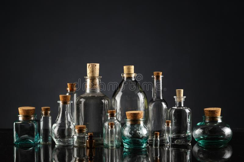 Glass bottles of different shapes and sizes on a black background. Object liquid transparent table product empty clean white container isolated beverage clear royalty free stock images