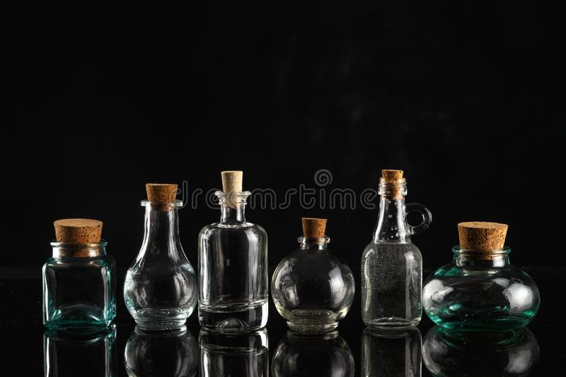 Glass bottles of different shapes and sizes on a black background. Object liquid transparent table product empty clean white container isolated beverage clear stock photos