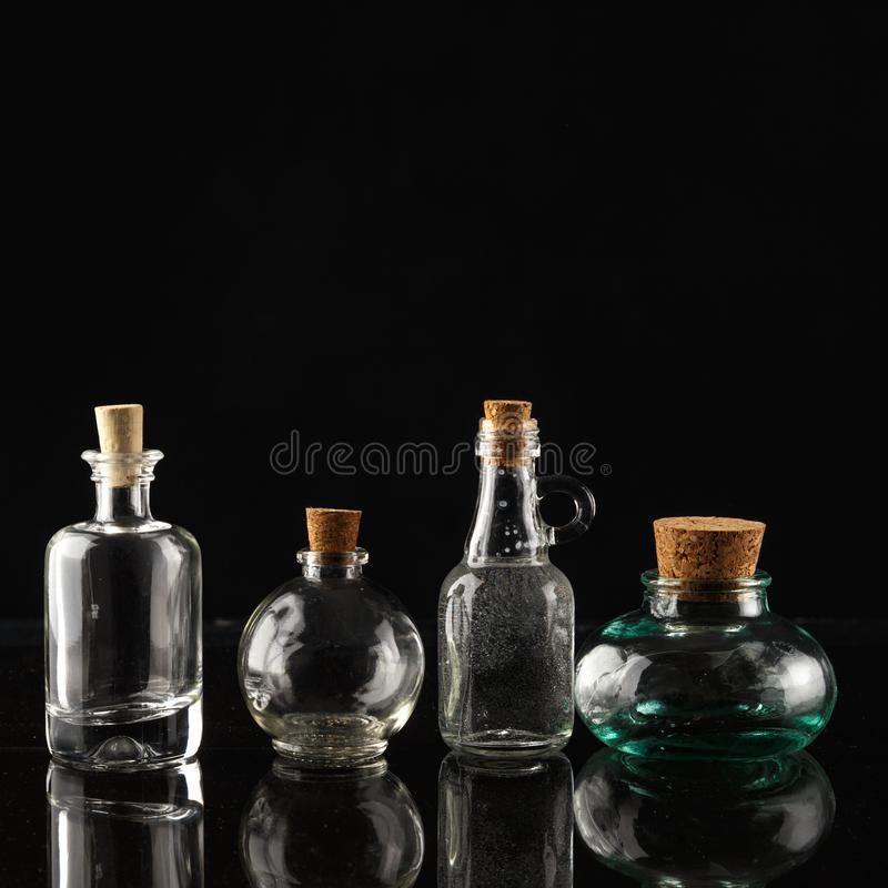 Glass bottles of different shapes and sizes on a black background. Object liquid transparent table product empty clean white container isolated beverage clear royalty free stock photo