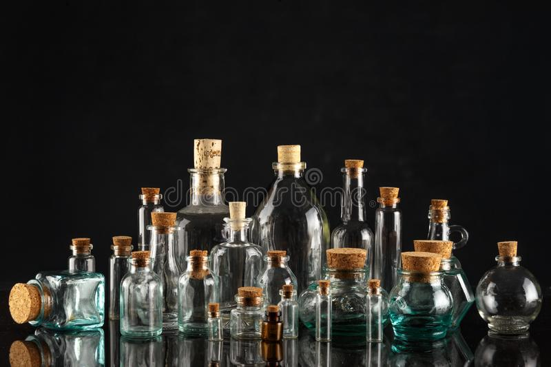 Glass bottles of different shapes and sizes on a black background. Object liquid transparent table product empty clean white container isolated beverage clear stock photography
