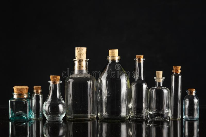 Glass bottles of different shapes and sizes on a black background. Object liquid transparent table product empty clean white container isolated beverage clear royalty free stock photography