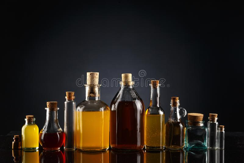 Glass bottles of different shapes and sizes filled with liquids of different colors on a black background. Object transparent table product empty clean white royalty free stock photo