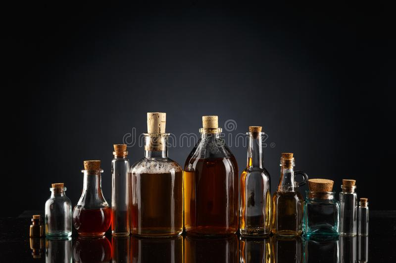 Glass bottles of different shapes and sizes filled with liquids of different colors on a black background. Object transparent table product empty clean white stock photos