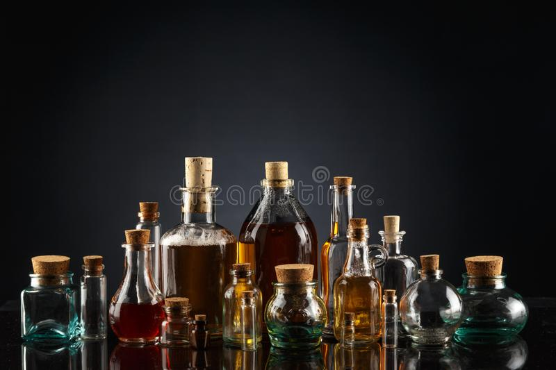 Glass bottles of different shapes and sizes filled with liquids of different colors on a black background. Object transparent table product empty clean white royalty free stock image