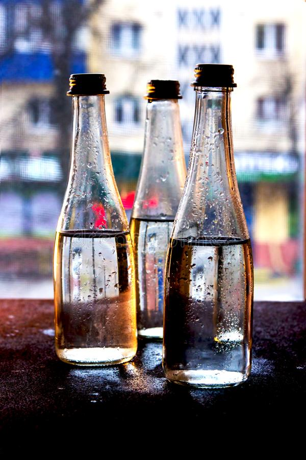 Glass bottles filled with half water in neon light on the background of the view from the window.  royalty free stock images