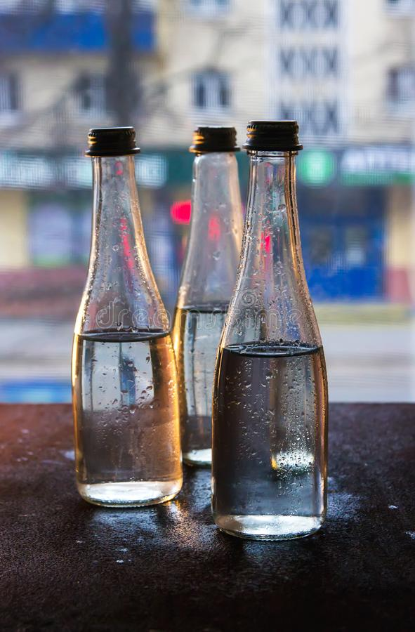 Glass bottles filled with half water in neon light on the background of the view from the window. Selective focus.  stock photo