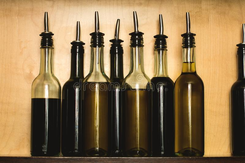 Glass bottles of healthy olive oils aligned on a home cupboard. Still life detail view of a wooden kitchen shelf with transparent royalty free stock photos