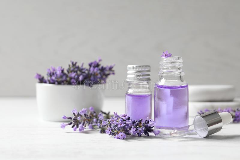 Glass bottles of natural cosmetic oil and lavender flowers on wooden table stock photo