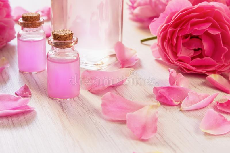Glass bottles with rose water and oil, rose flower petals on wooden rustic background. Close up stock photo