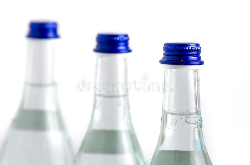 3 glass bottles in row filled with soda water with blue caps iso royalty free stock photo