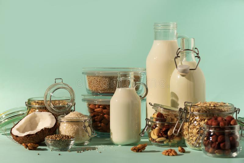 Glass bottles of vegan plant milk and almonds, nuts, coconut, hemp seed milk on blue background. Banner with copy space. Dairy. Free milk substitute drinks and stock photography