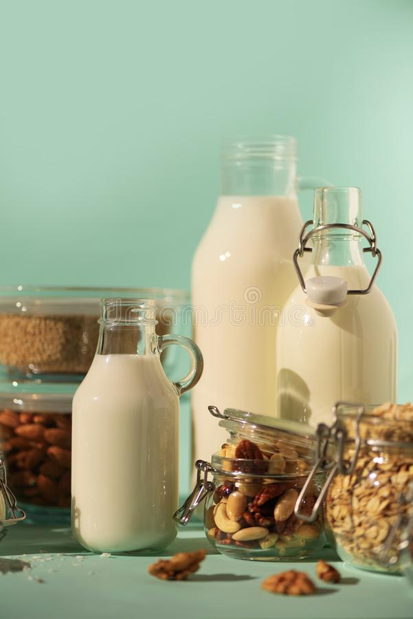 Glass bottles of vegan plant milk and almonds, nuts, coconut, hemp seed milk on blue background. Banner with copy space. Dairy. Free milk substitute drinks and stock photo