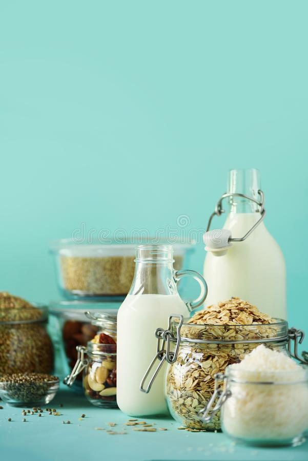Glass bottles of vegan plant milk and almonds, nuts, coconut, hemp seed milk on blue background. Banner with copy space. Dairy. Free milk substitute drinks and royalty free stock image