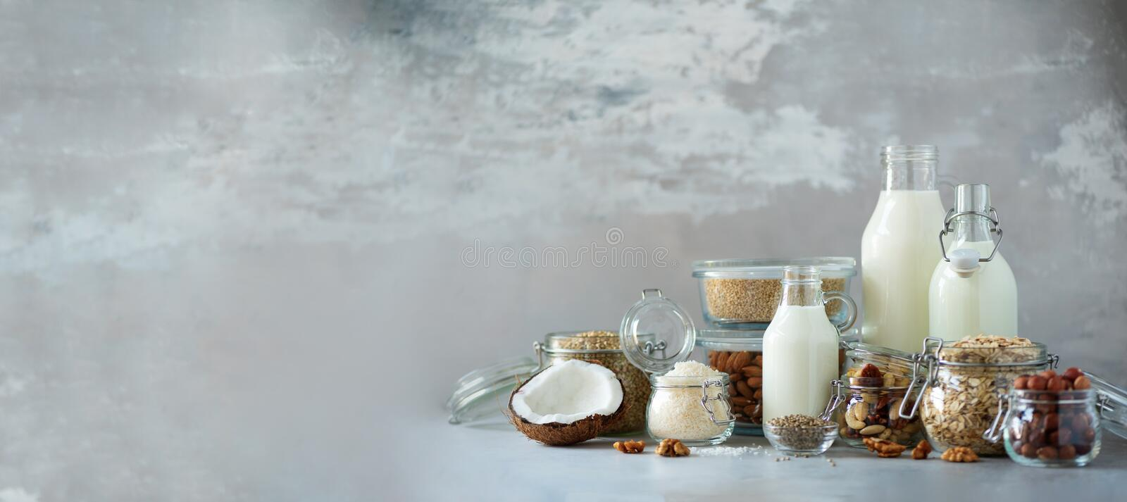 Glass bottles of vegan plant milk and almonds, nuts, coconut, hemp seed milk on grey concrete background. Banner with copy space. Dairy free milk substitute stock photos