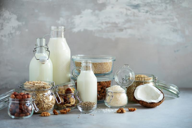 Glass bottles of vegan plant milk and almonds, nuts, coconut, hemp seed milk on grey concrete background. Banner with copy space. Dairy free milk substitute royalty free stock photo