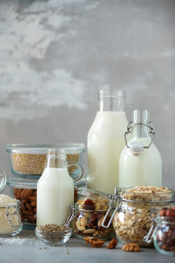 Glass bottles of vegan plant milk and almonds, nuts, coconut, hemp seed milk on grey concrete background. Banner with copy space. Dairy free milk substitute stock image