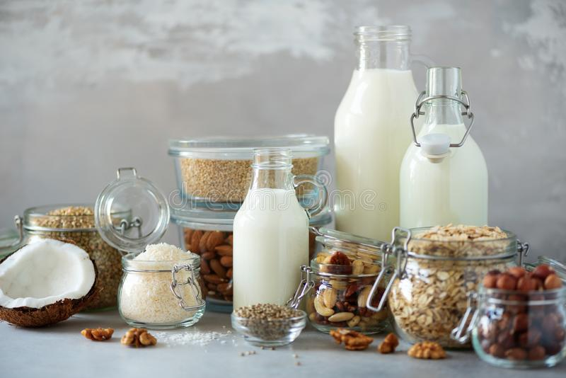 Glass bottles of vegan plant milk and almonds, nuts, coconut, hemp seed milk on grey concrete background. Banner with copy space. Dairy free milk substitute royalty free stock image