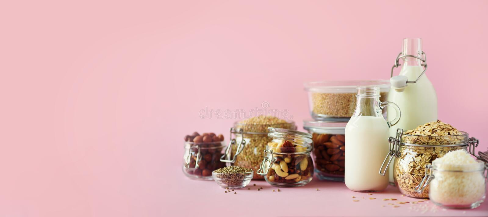 Glass bottles of vegan plant milk and almonds, nuts, coconut, hemp seed milk on pink background. Banner with copy space. Dairy. Free milk substitute drinks and stock photos