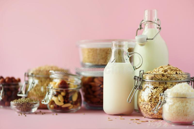 Glass bottles of vegan plant milk and almonds, nuts, coconut, hemp seed milk on pink background. Banner with copy space. Dairy. Free milk substitute drinks and stock image