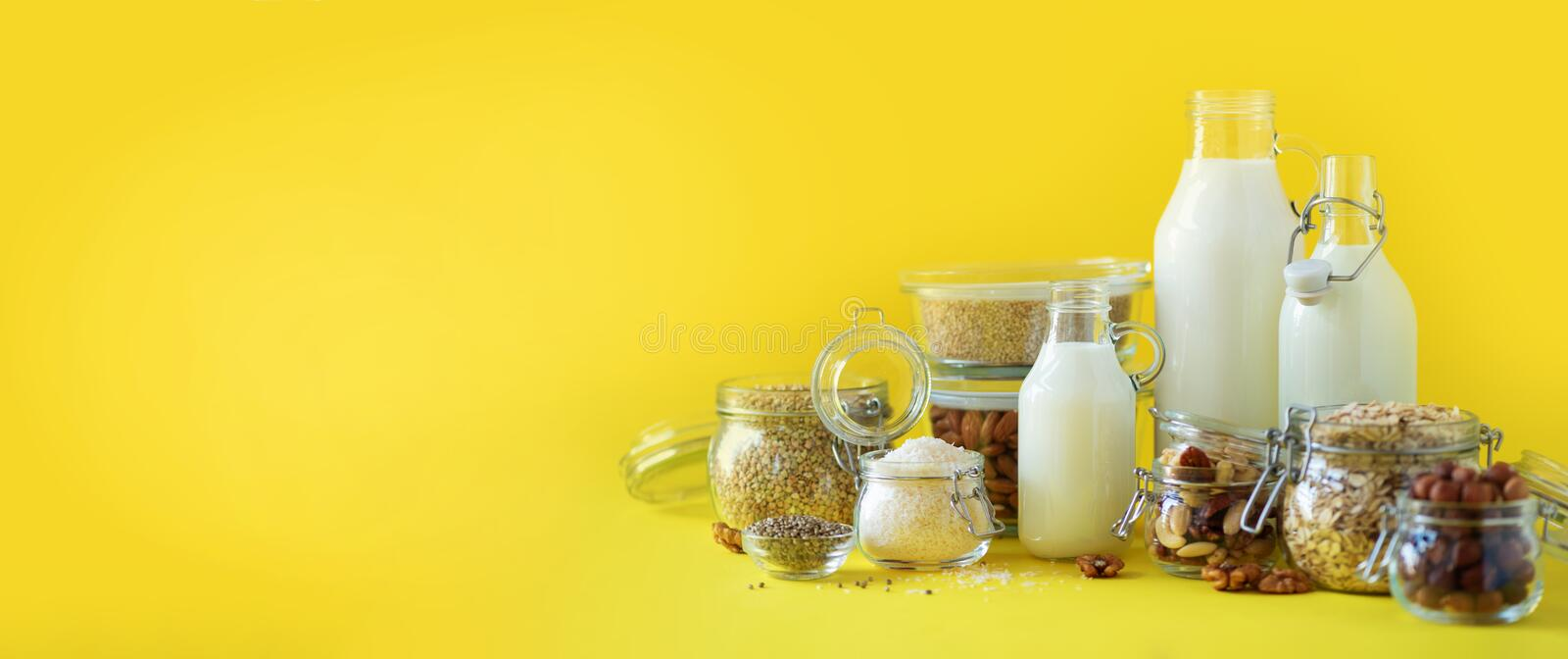 Glass bottles of vegan plant milk and almonds, nuts, coconut, hemp seed milk on yellow background. Banner with copy space. Dairy. Free milk substitute drinks royalty free stock photography
