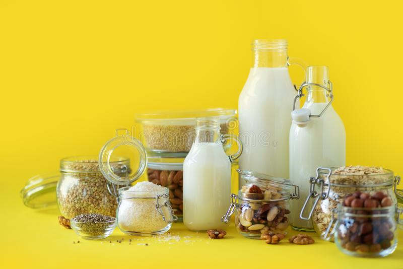 Glass bottles of vegan plant milk and almonds, nuts, coconut, hemp seed milk on yellow background. Banner with copy space. Dairy. Free milk substitute drinks stock photos