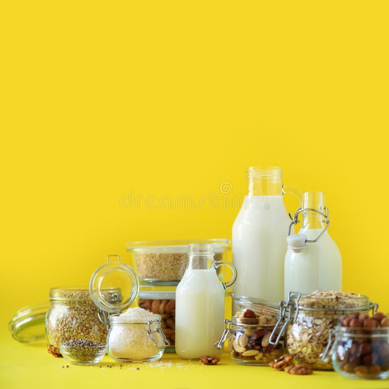 Glass bottles of vegan plant milk and almonds, nuts, coconut, hemp seed milk on yellow background. Banner with copy space. Dairy. Free milk substitute drinks royalty free stock images