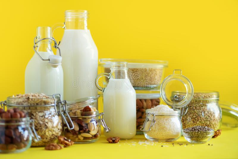 Glass bottles of vegan plant milk and almonds, nuts, coconut, hemp seed milk on yellow background. Banner with copy space. Dairy. Free milk substitute drinks stock images