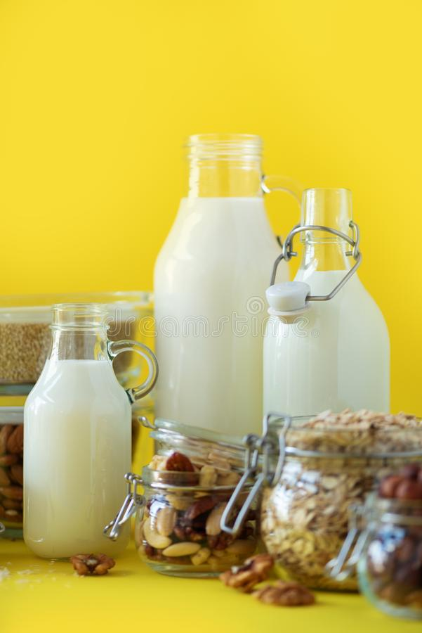 Glass bottles of vegan plant milk and almonds, nuts, coconut, hemp seed milk on yellow background. Banner with copy space. Dairy. Free milk substitute drinks royalty free stock photo