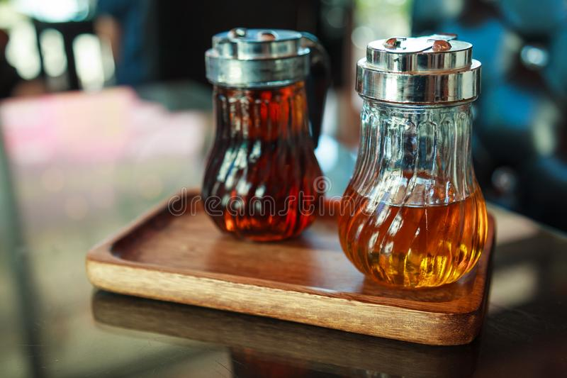 Glass bottles in wooden tray on table, containing hazelnut and caramel liquid syrups for flavoring coffee, drink and sweet dessert royalty free stock photography