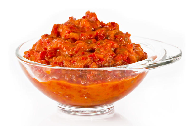 Glass bowl with ajvar. Transparent glass bowl full of delicious ajvar, on a white background royalty free stock photo
