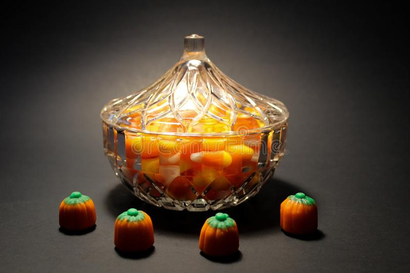 Glass bowl of candy corn on black background royalty free stock photos