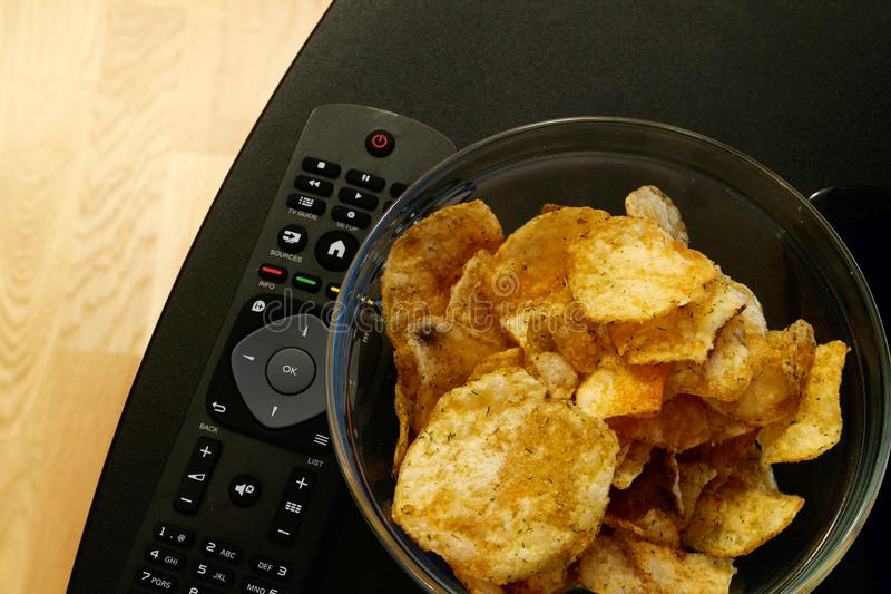 Glass bowl filled with dill and chive potato chips and a Tv remote on a black Tv stand. A glass bowl filled with crunchy dill and chive potato chips stands next royalty free stock images
