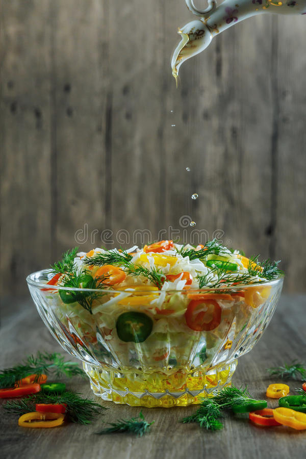 Glass bowl filled with organic super food salad with olive oil,. Red wine vinegar and forks stock photography