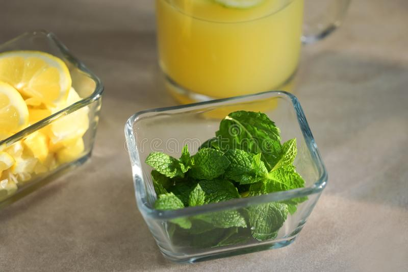 Glass bowl with fresh mint for lemon drink on table stock image