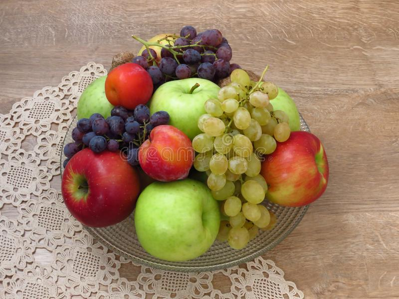 A glass bowl of fresh organic autumn fruit on crochet table cloth and oak wood table background. royalty free stock image