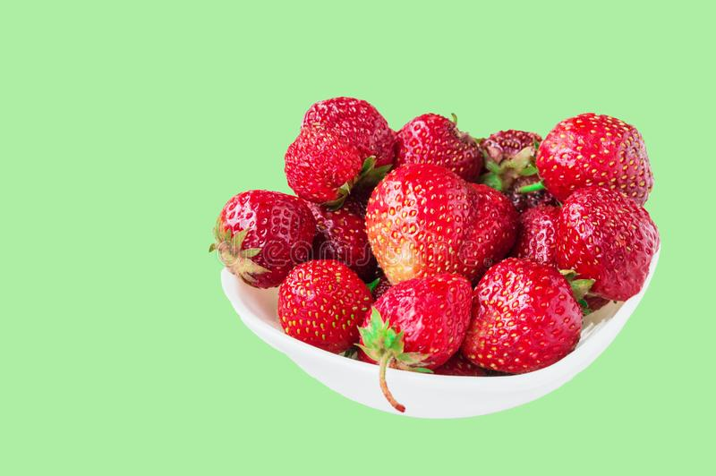 Glass bowl with fresh ripe strawberries, space for text, copy space isolated on green background, layout, clipping. Summer, outdoor, strawberry, fruit, tasty stock photography