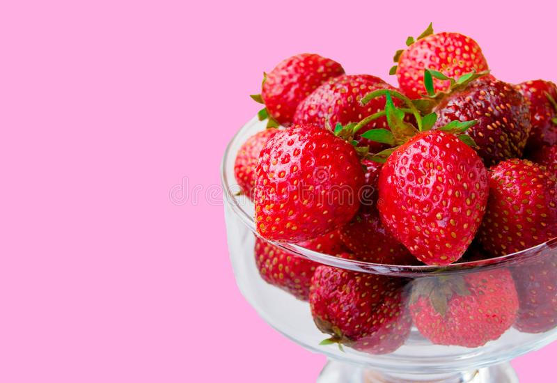 Glass bowl with fresh ripe strawberries, space for text, copy space isolated on pink background, layout, clipping. Summer outdoor strawberry fruit delicious red royalty free stock photo