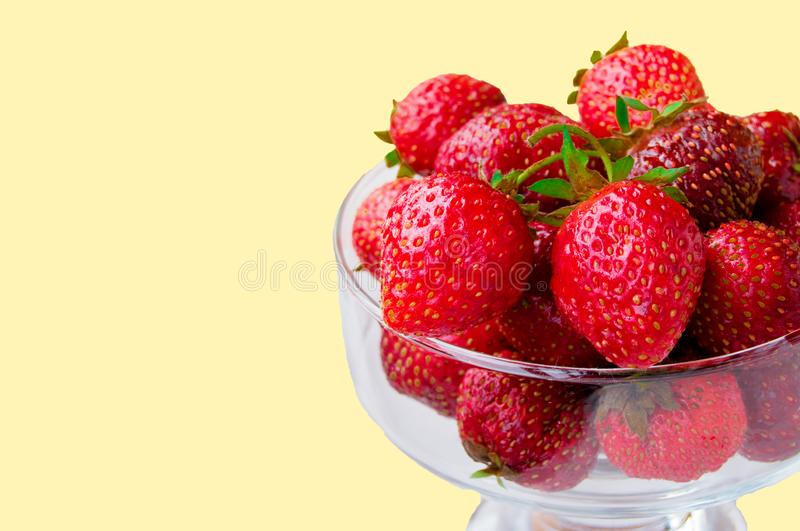 Glass bowl with fresh ripe strawberries, space for text, copy space isolated on yellow background, layout, clipping. Summer outdoor strawberry fruit delicious stock images