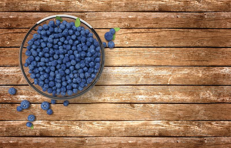 Glass bowl full of blueberries on wooden table royalty free stock images