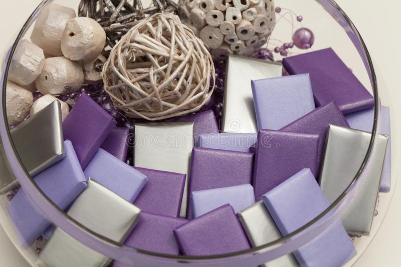 Round glass bowl full of wrapped chocolates and decorations stock photography