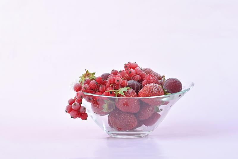 Glass bowl full of frozen red fruit royalty free stock photo