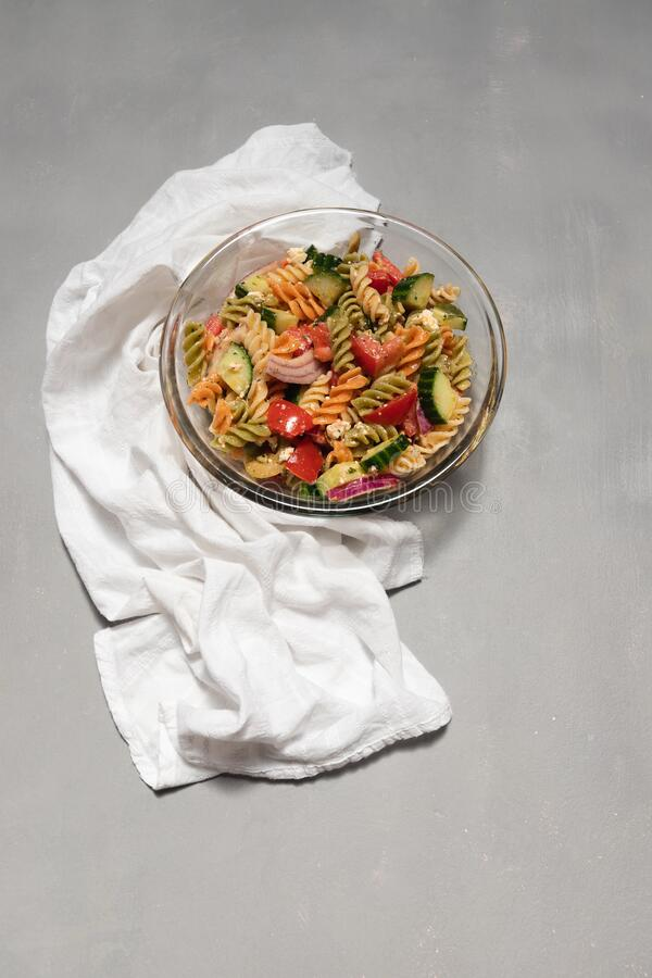 Glass bowl full of pasta salad with fusilli, feta cheese, veggies and olive oil dressing. White cloth on the side, and grey. Distressed background. refreshing royalty free stock photography