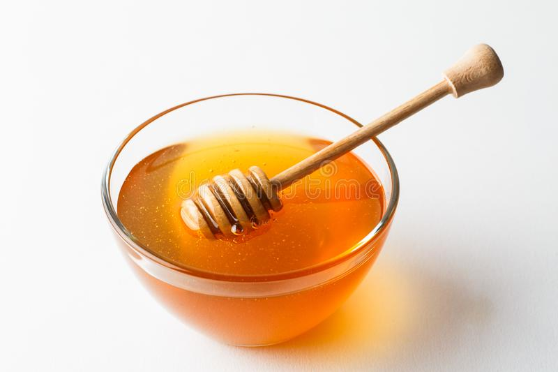 Glass bowl with honey and wooden dripper spoon on white background, organic product.  royalty free stock image