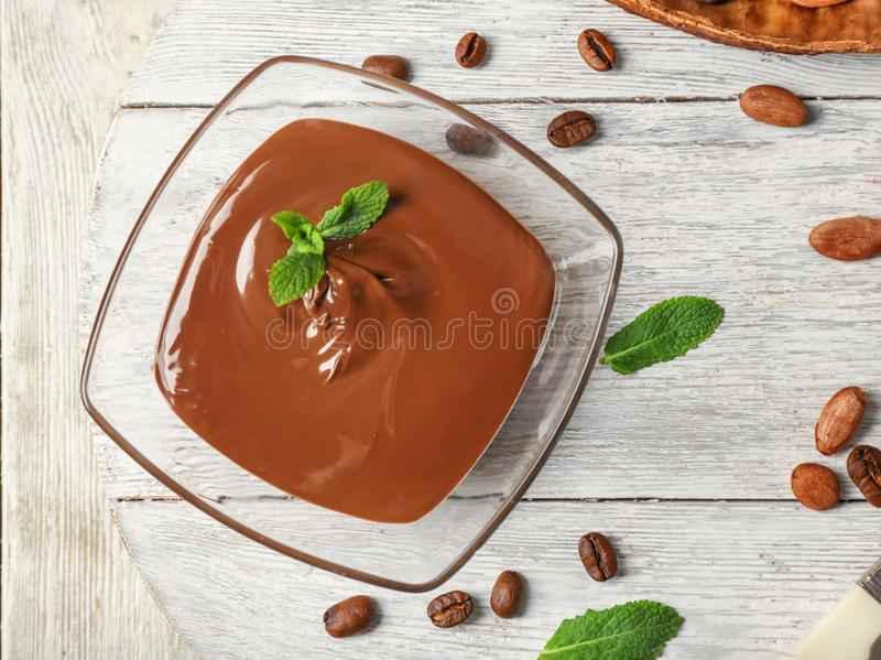 Glass bowl with molten chocolate on wooden table royalty free stock photo
