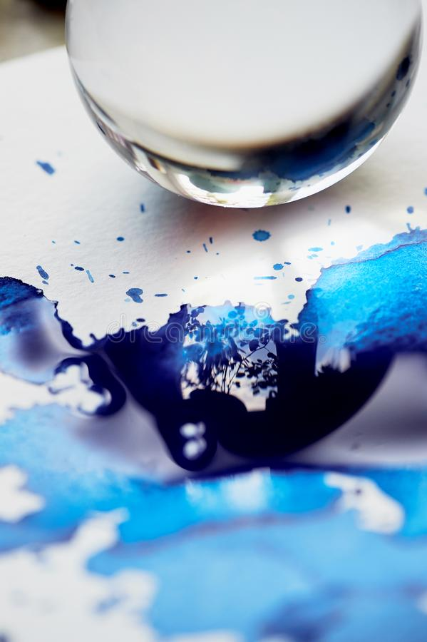 Glass bowl and reflection in blue ink puddle.Abstraction. Glass bowl and reflection in blue ink puddle. Abstraction royalty free stock image