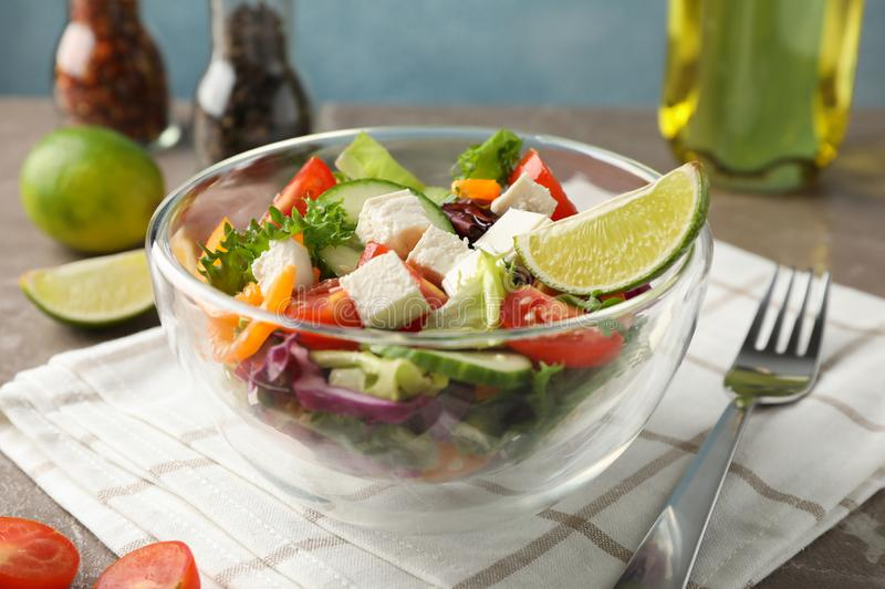 Glass bowl with salad, towel and spices on grey background. Space for text royalty free stock image