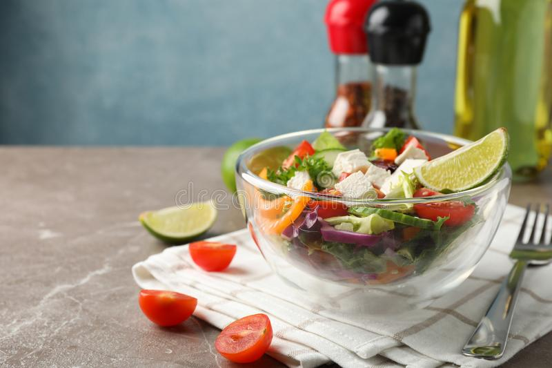 Glass bowl with salad, towel and spices on grey background. Space for text stock photos