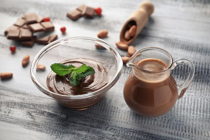 Glass bowl with tasty melted chocolate and jug of cocoa drink on wooden table royalty free stock photos
