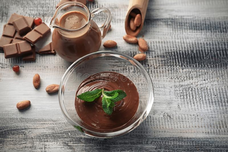 Glass bowl with tasty melted chocolate on wooden table royalty free stock photography