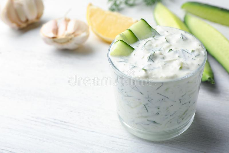 Glass bowl of Tzatziki cucumber sauce with ingredients. On wooden background, space for text royalty free stock photos